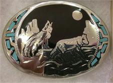 Southwestern belt buckle with wolves howling at the moon accented with turquoise.